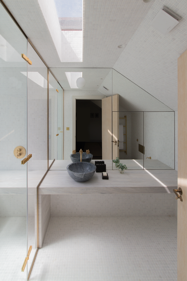 marble counter and mosaic walls beside walk-in shower